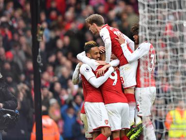 Pemain Arsenal merayakan gol yang diciptakan Pierre-Emerick Aubameyang saat melawan Stoke City dalam pertandingan Liga Inggris di Stadion Emirates, London (4/1). Arsenal 3-0 menang atas Stoke City. (AFP Photo/Oliver Greenwood)