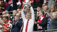 Arsene Wenger memegang trofi Piala FA 2016-2017 di Stadion Wembley, London, Sabtu (27/5). Arsenal mengalahkan Chelsea 2-1 dalam laga final tersebut. (AP Photo)
