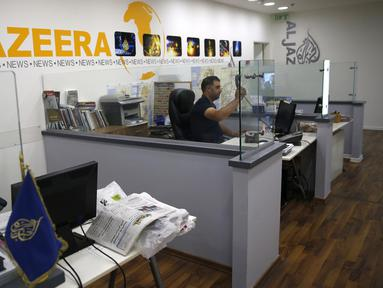 Seorang karyawan berada di balik mejanya di kantor berita Al Jazeera, Yerusalem, 31 Juli 2017. Kementerian Komunikasi Israel mengumumkan rencana menutup kantor Aljazeera di Yerusalem dan melarang kegiatan jurnalisnya. (AHMAD GHARABLI / AFP)