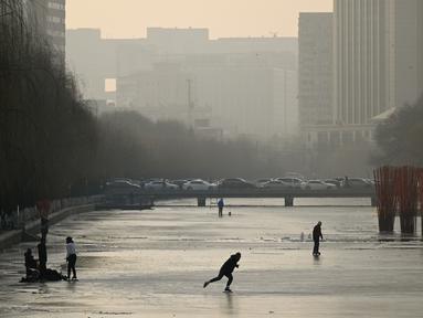 Sejumlah warga bermain ice skating di sungai yang membeku di Beijing, China (10/1). Akibat membeku, Sungai ini menjadi objek wisata dadakan. (AFP Photo/Wang Zhao)