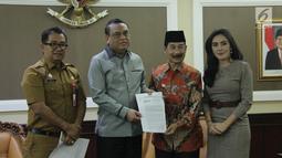 Menpan RB Syafruddin (kedua kiri) dan Bupati Kabupaten Solok Selatan Muzni Zakaria (kedua kanan) menunjukkan berkas CPNS dokter gigi Romi Syofpa Ismael di kantor Kemenpan RB, Jakarta, Senin (5/8/2019). (Liputan6.com/Angga Yuniar)