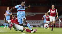 Gelandang West Ham, Michail Antonio membawa bola dari kawalan bek Arsenal,  Gabriel Magalhães pada pertandingan lanjutan Liga Inggris di Stadion Emirates di London, Inggris, Sabtu (19/9/2020). Arsenal menang tipis 2-1 atas West Ham. (Will Oliver/Pool via AP)