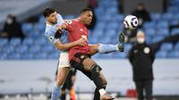 Striker Manchester United atau MU Anthony Martial dan pemain Manchester City Ruben Dias berebut bola dalam laga Liga Inggris di Etihad Stadium, Minggu (7/3/2021). (Peter Powell/Pool via AP)