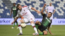 Penyerang AC Milan, Ante Rebic, berebut bola dengan gelandang Sassuolo, Mehdi Bourabia, pada laga lanjutan Serie A pekan ke-35 di Mapei Stadium, Rabu (22/7/2020) dini hari WIB. AC Milan menang 2-1 atas Sassuolo. (Massimo Paolone/LaPresse via AP)