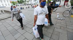 Warga menerima paket sembako usai acara kegiatan CSR Tiket Ramadan di Kota Tua Fatahillah, Jakarta, Kamis (06/05/2021). Kegiatan sosial bertajuk Beramal Bersama Teman menjelang Idul Fitri juga digelar di Yogyakarta dan Bali. (Liputan6.com/Fery Pradolo)
