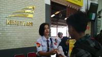 Ikko Erliana ketika bertugas mengawasi dan membantu penumpang di stasiun Cirebon. (foto : Liputan6.com /panji prayitno)