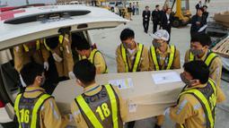 Petugas memasukkan peti mati berisi jenazah yang ditemukan tewas dalam truk kontainer di Inggris ke dalam ambulans setibanya di bandara internasional Noi Bai, Hanoi, Rabu (27/11/2019). Sebanyak 16 dari 39 jenazah telah tiba di Vietnam untuk dibawa ke kampung halaman masing-masing. (Nhac NGUYEN/AFP)
