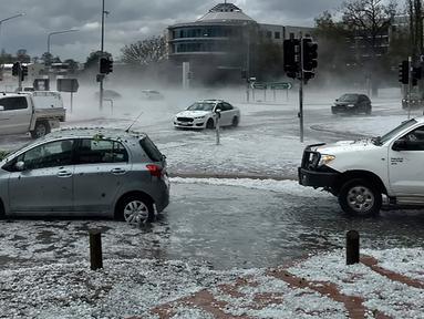 Huja es menutupi kendaraan di persimpangan jalan ibu kota Australia, Canberra pada Senin (20/1/2020). Badai petir dan hujan es menerjang bagian wilayah pantai timur Australia  setelah sebelumnya badai debu melanda daerah-daerah yang dilanda kekeringan. (Tom Swann/The Australia Institute via AP)