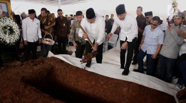 Presiden ke-6 Susilo Bambang Yudhoyono (SBY) disaksikan Agus Harimurti menaburkan tanah yang pertama kali ke makam sang ibu, Siti Habibah, di TPU Tanah Kusir Jakarta, Sabtu (31/8/2019). Ibunda SBY, almarhumah Siti Habibah meninggal pada Jumat (30/8) pukul 19.21 WIB. (merdeka.com/magang/Ahmad Sujana)