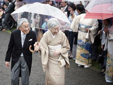 Kaisar Jepang Akihito dan Permaisuri Michiko menyambut para tamu saat pesta taman musim gugur di taman kekaisaran Akasaka Palace, Tokyo, Jumat (9/11). Kaisar dan Permaisuri tampil romantis dengan sepayung berdua saat hujan. (AP Photo/Eugene Hoshiko)