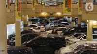 Dua orang terlihat di antara mobil bekas yang dijual di kawasan Jakarta, Senin (23/11/2020). Pasar mobil bekas diprediksi akan meningkat menjelang akhir tahun karena kondisi perekonomian yang saat ini mulai membaik. (Liputan6.com/Angga Yuniar)