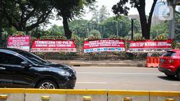 Kendaraan melintasi karangan bunga yang menghiasi kawasan Patung Kuda, Jakarta, Kamis (15/10/2020). Karangan bunga tersebut merupakan apresiasi masyarakat kepada TNI-Polri yang telah menjaga keamanan saat demo. (Liputan6.com/Faizal Fanani)
