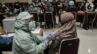Tenaga pendidik saat menerima vaksinasi Covid-19 di GOR Tanjung Priok, Jakarta Utara, Selasa (6/4/2021). Vaksinasi Covid-19 dilakukan sebagai upaya meningkatkan kekebalan kepada para pengajar jelang uji coba sekolah tatap muka. (merdeka.com/Iqbal S. Nugroho)