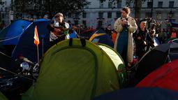 Seorang pria memainkan gitar saat aktivis iklim berkemah di Whitehall, London, Inggris, Selasa (8/10/2019). Protes global oleh gerakan Pemberontakan Kepunahan menuntut tindakan yang lebih mendesak untuk melawan perubahan iklim. (AP Photo/Alastair Grant) (AP Photo/Hibah Alastair)