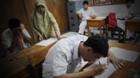 Seorang siswa Tuna Netra peserta Ujian Nasional tingkat SMA di SLB Negeri Beringin Purwakarta, Jawa Barat kemarin harus dibantu guru yang bisa membacakan huruf braile.