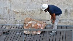 Pekerja Otoritas Pengurus Benda Antik Israel memeriksa batu besar yang jatuh dari Tembok Ratapan di Kota Tua Yerusalem, Rabu (25/7). Rabbi Tembok Ratapan menyebut kejadian ini langka dan belum pernah muncul dalam berpuluh-puluh tahun. (AFP/AHMAD GHARABLI)