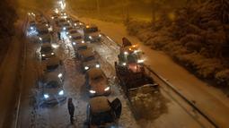 Sejumlah mobil terjebak salju tebal yang menyelimuti Jalan Lingkar M30 di Madrid, Spanyol, Jumat (8/1/2021). Badai Filomena mengakibatkan salju lebat turun di Madrid dan sebagian besar wilayah Spanyol. (OSCAR DEL POZO/AFP)