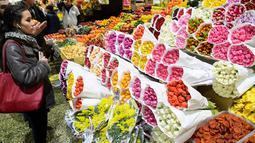 Seorang wanita melihat bunga jelang Hari Perempuan Internasional di pasar bunga Moskow (5/3). Hari Perempuan Internasional pertama kali dirayakan tanggal 28 Februari 1909 di New York dan diselenggarakan Partai Sosialis AS. (AFP Photo/Kirill Kudryavtsev)