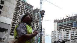 Pekerja memantau pembangunan Kompleks Wisma Atlet Kemayoran, Jakarta, Kamis (29/12). Rusun ini terdiri dari 10 tower dengan jumlah unit 7.424. (Liputan6.com/Faizal Fanani)