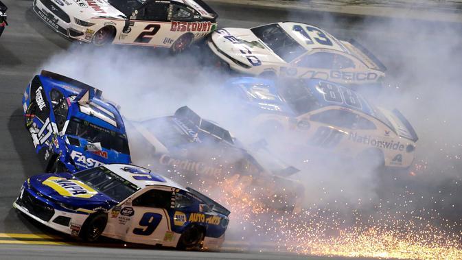 Sejumlah mobil terlibat kecelakaan dalam balapan NASCAR Daytona 500 di Daytona International Speedway, Daytona Beach, Florida, AS, Minggu (17/2). Kru bekerja keras untuk membersihkan serpihan mobil yang terlibat kecelakaan. (AP Photo/Gary McCullough)
