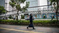 Seorang perempuan melintasi trotoar di Jalan Sudirman, Jakarta Pusat, Rabu (6/1/2021). Selama pembatasan sosial berskala besar (PSBB) di wilayah Jawa dan Bali pada 11-25 Januari 2021, aktivitas bekerja di kantor diperketat dengan sistem work from home (WFH) 75 persen. (Liputan6.com/Faizal Fanani)