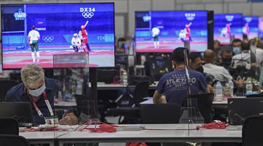 Wartawan beraktivitas di dalam Main Press Center (MPC) Olimpiade Tokyo 2020 di Tokyo pada Kamis (22/7/2021). Main Press Center mulai ramai dengan para jurnalis dari berbagai negara jelang pembukaan Olimpiade Tokyo 2020 pada 23 Juli mendatang. (Martin BERNETTI / AFP)