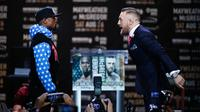 Juara mixed martial arts Conor McGregor (kiri) dan petinju Floyd Mayweather Jr bertatapan saat jumpa pers di Staples Center Los Angeles, AS (12/7). Mayweather dan McGregor akan bertanding pada 26 Agustus 2017. (AP Photo/Jae C. Hong)