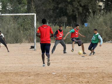 Sejumlah pria bermain sepak bola di lapangan tanah sebelum buka puasa selama bulan Ramadhan, di ibu kota Libya, Tripoli (24/4/2021). (AFP/Mahmud Turkia)