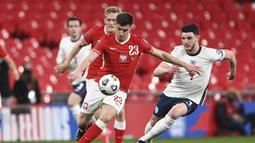 Striker Polandia, Krzysztof Piatek (kiri) menguasai bola dibayangi bek Inggris, Declan Rice dalam laga lanjutan Kualifikasi Piala Dunia 2022 Zona Eropa Grup I di Wembley Stadium, London, Rabu (31/3/2021). Polandia kalah 1-2 dari Inggris. (AP/Andy Rain)