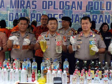 Kapolda Metro Jaya Irjen Pol Idham Azis (tengah) dan jajaraannya menunjukkan barang bukti saat rilis hasil operasi miras di Polda Metro Jaya, Jakarta, Jumat (20/4). Jajaran Polda Metro Jaya berhasil menyita 39.834 botol miras. (Liputan6.com/Arya Manggala)