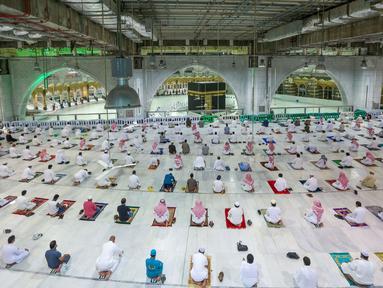 "Warga Saudi dan ekspatriat melakukan sholat ""Al Fajr"" di Masjidil Haram di kota suci Mekkah (18/10/2020). Arab Saudi akhirnya mengizinkan warganya menjalankan salat di Masjidil Haram untuk pertama kalinya sejak pandemi Covid-19. (AFP/STR)"