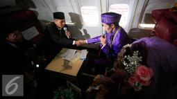 Penghulu menikahkan sepang mempelai pada prosesi nikah massal di kampus STTKD, Yogyakarta, Senin (4/4/2016). Sebanyak 21 pasangan pengantin mengikuti nikah bareng angkasa di atas pesawat boing. (Liputan6.com/Boy Harjanto)