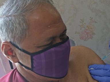 Warga lanjut usia (lansia) menjalani vaksinasi Covid-19 di Puskesmas Kecamatan Senen, Jakarta Pusat, Selasa (23/2/2021). Pelaksanaan vaksinasi Covid-19 sudah masuk pada tahap 2 yang diperuntukan bagi Lansia dan petugas pelayanan publik. (Liputan6.com/Herman Zakharia)