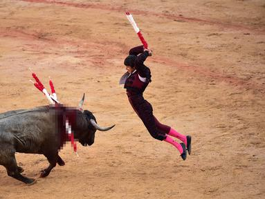 Matador Spanyol Joao Ferreira melompat untuk menusuk banteng saat bertarung dalam Festival San Fermin, Pamplona, Spanyol, Selasa (9/7/2019). (AP Photo/Alvaro Barrientos)