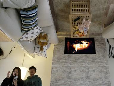 Pengunjung melihat-lihat bagian dalam rumah terbalik di Huashan Creative Park, Taipei, Taiwan, Selasa (8/3/2016). Bangunan unik ini berdiri terbalik dengan luas sekitar 300-an meter persegi dan dibuka untuk umum hingga 22 Juli mendatang. (SAM YEH/AFP)