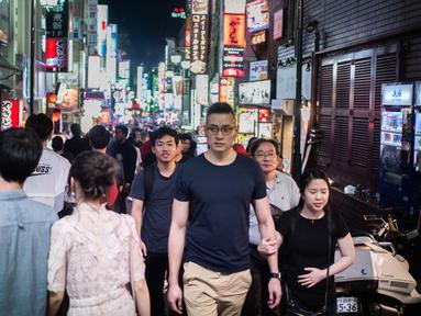 Foto yang diambil pada 22 September 2018 menunjukkan orang-orang berjalan di distrik Shinjuku, Tokyo. Distrik Shinjuku dikenal sebagai kawasan perbelanjaan dan hiburan malam Jepang. (AFP PHOTO / Martin BUREAU)