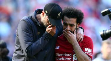 Manajer Liverpool Juergen Klopp (kiri) berbicara dengan Mohamed Salah yang menangis usai laga Liga Inggris menghadapi Wolverhampton Wanderers di di Stadion Anfield, Liverpool, Inggris, Minggu (12/5/2019). Liverpool gagal meraih gelar juara Liga Inggris. (AP Photo/Dave Thompson)