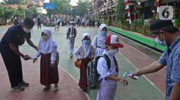 Petugas mengecek suhu badan para siswa setibanya di SDN 05 Kalisari, Jakarta, Senin (30/8/2021). Pemprov DKI menggelar pembelajaran tatap muka di tengah pandemi covid-19 mulai 30 Agustus 2021 secara terbatas dengan kapasitas 50 persen pada setiap satuan pendidikan. (Liputan6.com/Herman Zakharia)