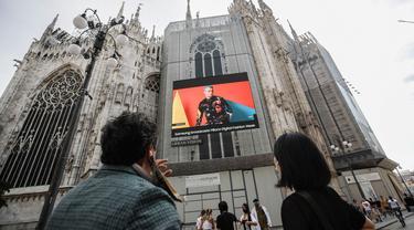 Pejalan kaki melewati layar di katedral Duomo yang menunjukkan model Moschino selama Milan Digital Fashion Week, di Milan, Italia, 14 Juli 2020. Empat puluh rumah mode menampilkan koleksi pakaian untuk musim semi/musim panas 2020 dalam format digital di tengah pandemi Covid-19. (AP Photo/Luca Bruno)