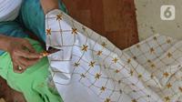 Perajin menyelesaikan salah satu tahapan produksi batik Marunda di Rusunawa Marunda, Jakarta, Selasa (14/7/2020). Batik Marunda merupakan kreasi para ibu di tiga rusun sewa. (Liputan6.com/Herman Zakharia)