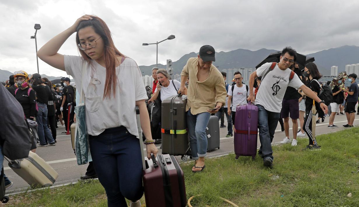 Penumpang berjalan kaki ke bandara ketika pemrotes pro-demokrasi memblokir jalan di luar bandara di Hong Kong (1/9/2019). Demonstran pro-demokrasi penentang RUU Ekstradisi kembali menjadikan bandara sebagai tempat aksi demo. (AP Photo/Kin Cheung)