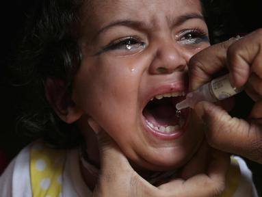 Seorang anak menangis saat diberikan vaksin polio oleh pekerja kesehatan di Lahore, Pakistan, (9/4). Pakistan meluncurkan vaksinasi polio baru, yang bertujuan agar 38,7 juta anak di bawah usia 5 tahun mendapatkan vaksin tersebut. (AP Photo/KM Chaudary)