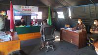 Salah satu pelanggar PPKM Darurat tengah mengikuti jalannya sidang Tipiring di tenda Posko penegakan hukum PPKM Darurat di bilangan Simpang Lima, Garut, Jawa Barat. (Liputan6.com/Jayadi Supriadin)