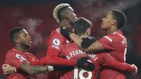 Gelandang Manchester United, Bruno Fernandes (18) berselebrasi dengan rekan-rekannya usai mencetak gol ke gawang Aston Villa pada pertandingan lanjutan Liga Inggris di stadion Old Trafford, Inggris  (2/1/2021). Kini, MU mengoleksi 33 poin, sama dengan milik Liverpool. (Carl Recine/ Pool via AP)
