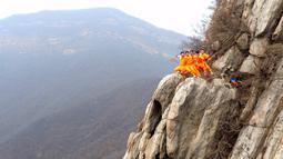 Sejumlah murid dari sekolah bela diri berlatih kungfu Shaolin di ujung tebing gunung  Songshan, , China , (17/3). Tanpa dibekali alat keamanan, Para murid ini melakukan gerakan ekstrem di tebing gunung. (REUTERS / China Daily)