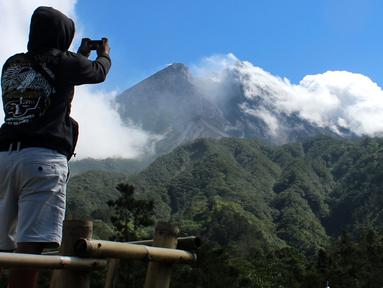 Seorang pria mengambil gambar Gunung Merapi di Cangkringan, Indonesia, Selasa, (22/5). Pihak berwenang meningkatkan kewaspadaan terhadap Gunung Merapi yang bergejolak di pulau Jawa. (AP Photo/A.K. Hendratmo)