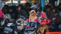 Seorang anak duduk di atas motor saat menanti waktu masuk kapal penyebrangan di Dermaga 1 Pelabuhan Penyebrangan Merak, Banten, Sabtu (1/6/2019). Meski berbahaya, pemudik tetap nekat membawa anak berkendara sepeda motor menuju kampong halaman. (Liputan6.com/Helmi Fithriansyah)