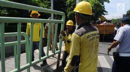 Petugas membongkar pagar pembatas besi di kawasan Pinang Ranti, Jakarta, Senin (11/2). Zebra cross yang berada di samping Tamini Square itu sempat jadi perbincangan lantaran terhalang oleh pagar besi hijau setinggi 1 meter. (Liputan6.com/Herman Zakharia)