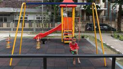 Seorang anak bermain ayunan di RPTRA Tiga Durian, Jakarta, Selasa (15/5). Pembangunan Taman Maju Bersama rencananya akan dimulai pada Mei 2018 dengan anggaran pembangunan sekitar Rp 27 miliar. (Liputan6.com/Immanuel Antonius)