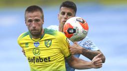 Bek Manchester City, Joao Cancelo, berebut bola dengan pemain Norwich City, Marco Stiepermann, pada laga Premier League di Stadion Etihad, Minggu (26/7/2020). Manchester City menang dengan skor 5-0. (AP Photo/Dave Thompson, Pool)
